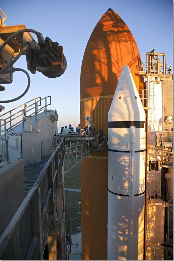 Na plataforma de lançamento, trabalhadores removem a linha de ventilação ligada à placa de suporte umbilical do solo no tanque externo de combustível do Discovery (Foto: Martin Frankie / NASA)