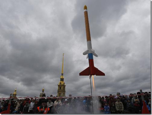 Multidão assiste ao lançamento de um modelo de foguete em São Petersburgo, Rússia, com a Catedral de São Pedro e São Paulo ao fundo; evento faz parte das comemorações (Foto: AP Photo/Dmitry Lovetsky)