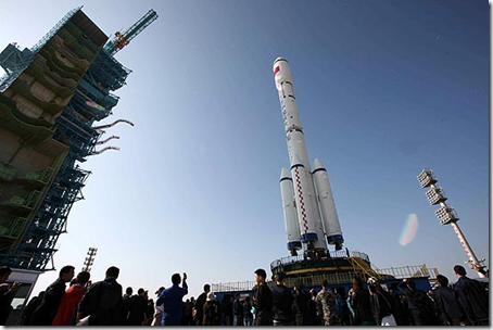 Turistas observam o foguete Longa Marcha 2F, que transporta o primeiro módulo da estação chinesa (Foto: France Presse)