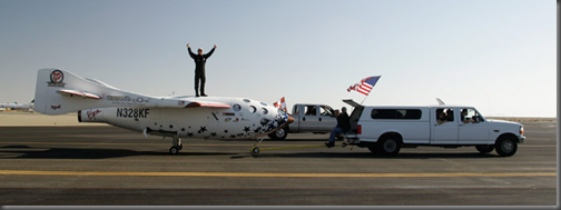 Piloto Mike Melvill celebra o sucesso de seu voo espacial privado com a SpaceShipOne sobre a nave (Foto: Mike Massee)