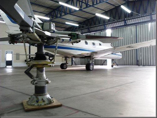 Aeronave Falcon 10 e rotor principal de helicóptero no interior do hangar da EMCA (Foto: Eduardo Oliveira)