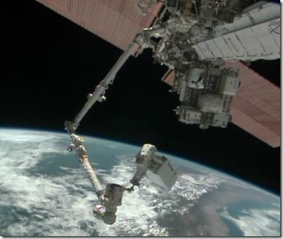 Mike Hopkins na ponta do braço robótico da ISS sobre o Peru em EVA na véspera de Natal (Foto: NASA TV)