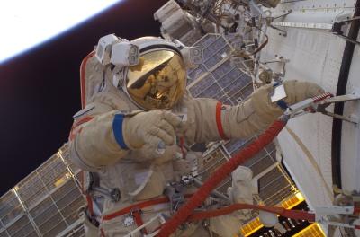 Dentro de um Orlan-M, John Phillips realiza EVA na ISS; em seu viro, o reflexo de Sergei Krikalev  (Foto: NASA)